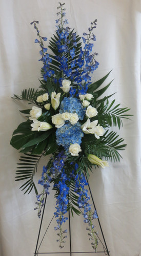 The Ocean Blue Funeral Flowers Spray by Enchanted Florist Pasadena TX is a beautiful blue and white sympathy standing spray of flowers.  It includes blue delphinium, blue hydrangeas, white lilies and white roses with accent foliages. RM544