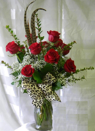 Wild About You Red Roses by Enchanted Florist Pasadena TX.Classic dozen red roses with a flair or leopard and feathers. Our premium Ecuadorian roses in red, with premium tropical foliages, baby's breath, pheasant feathers, and a wired leopard print bow. RM353