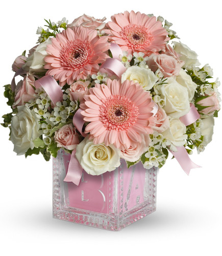 New Baby Girls First Crystal Block with Flowers by Enchanted Florist Pasadena TX. Baby's first building block is complete with a lovely assortment of delicate flowers to welcome any new baby girl in to the world. Includes pink gerbera daisies, white spray roses and pink spray roses. Just lovely! SKU RM310