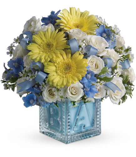 Baby Boys First Block with Flowers by Enchanted Florist Pasadena TX. Baby's first building block is complete with a lovely assortment of delicate flowers to welcome any new baby boy in to the world. Includes yellow gerbera daisies, white spray roses and the blue flowers are delphinium. Just lovely! RM178