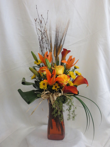 Autumn Excellence Yellow Rose Flower Bouquet by Enchanted Florist Pasadena TX. A beautiful fall bouquet of flowers and includes orange lilies, yellow roses, orange mini calla lilies, and yellow vikings accented with branches, wheat, leaves and grasses. The bouquet comes expertly designed in a orange vase with a raffia bow.  RM188