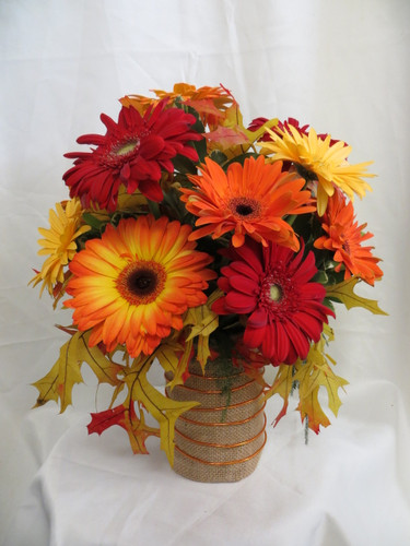 Autumn Magic Gerbera Bouquet by Enchanted Florist Pasadena TX. This lovely fall all gerbera daisy bouquet includes a mixture of fall colored gerbera daisies of red, yellow, and oranges arranged in a burlap vase accented with orange wire and fall leaves. RM207