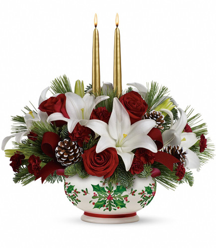 "Send your very best wishes for a memorable holiday season with this luxurious gift of red roses, snow white lilies and classic winter greens, hand-delivered in an elegant ceramic bowl. Golden taper candles lend a touch of shimmer to this sensational centerpiece.  This festive arrangement of red roses, white asiatic lilies, miniature maroon carnations, noble fir, and white pine is adorned with burgundy velvet ribbon, frosted pinecones and golden taper candles. Delivered in a Holly Days bowl. Approximately 18"" W x 17 1/2"" H"
