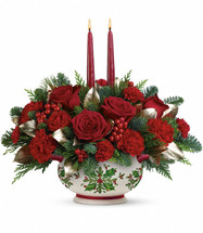 "A gift they'll treasure this Christmas and every winter to come! Hand-delivered in a lovely ceramic bowl adorned with a classic holly motif, this lush centerpiece of red roses and festive winter greens captures the warm glow of two elegant taper candles.  This fresh, festive arrangement includes red roses, red carnations, red miniature carnations, white pine, noble fir, flat cedar, lemon leaf, red berries and taper candles. Delivered in a Holly Days bowl. Approximately 17 1/2"" W x 16 1/2"" H"