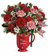 "Warm their hearts this holiday with this merry mug! Overflowing with happy holiday blooms including red and peppermint carnations, it's a charming Christmas keepsake that will serve up hot, steaming cocoa for years to come. Even includes its very own stirring spoon!  This tasty bouquet includes red carnations, peppermint carnations, red miniature carnations, white sinuata statice, variegated holly, noble fir, white pine, and frosted pinecones. Delivered in a Merry Mug. Approximately 12 1/4"" W x 13 1/2"" H"