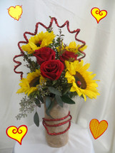 Sunburst Love Bouquet for Valentines Day by Enchanted Florist Pasadena TX.   These sunny sunflowers and red roses are sure to brighten anyone's day. This Valentines Day bouquet is hand crafted in a burlap covered vase and accented with red sequence glittered rope. RM931