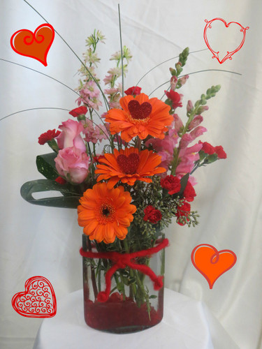 Unforgettable Valentines Day Flowers by Enchanted Florist in Pasadena TX.  This bouquet is expertly designed in our exclusive eyelash vase and accented with red rocks and red wool. The flowers include orange gerbera daisies, hot pink roses, pink snapdragons, and other coordinating flowers. RM930