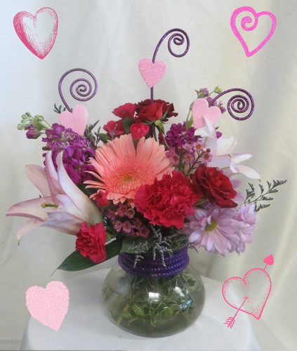 Eclipse of the Heart Bouquet for Valentines Day by Enchanted Florist Pasadena TX. Styled in our rosie posie vase, this Valentines Day bouquet of flowers includes pink gerberas, lavender stock, and red spray roses. RM928