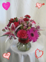 Starstruck Bouquet for Valentines Day by Enchanted Florist Pasadena TX. Let her be starstruck with you when she receives this Valentines Day gifts.  Expertly designed in our rosie posie vase and accented with red mesh rope. Flowers include pink roses, stargazer lilies, and other red and hot pink flowers. RM927