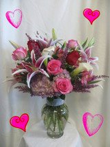 Rhapsody in Pink for Valentines Day by Enchanted Florist Pasadena TX. This beautiful Valentines bouquet includes red and pink roses, stargazer lilies, lavender hydrangeas, white calla lilies and the vase is accented with faux diamond collar. RM926
