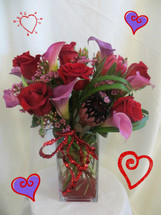 Madly In Love Tropical Bouquet by Enchanted Florist Pasadena TX.  Includes red roses, protea, and purple mini calla lilies in a clear vase with red rocks at the bottom for extra pops of color. RM924