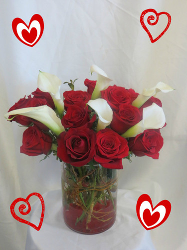 Embrace Me Red Roses & White Calla Lilies by Enchanted Florist Pasadena TX. This luscious bouquet arrives in a contemporary cylinder vase accented with red rocks and is filled with 16 red roses and white miniature calla lilies. RM922