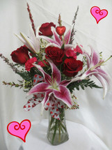 Twilight Romance Valentines Day Bouquet by Enchanted Florist Pasadena TX. Fragrant stargazer lilies and red roses arranged in a clear glass vase with hot pink mini carnations, and other romantic filler flowers. RM938