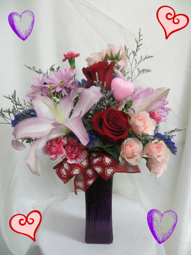 Perfectly Purple Love Bouquet by Enchanted Florist Pasadena TX. Purple, lavenders, pinks, and reds create a beautiful bouquet of love flowers for this Valentines Day occasion. Designed in this purple vase, she will absolutely love it! RM939