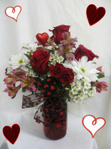 Country Love for Valentines Day by Enchanted Florist Pasadena TX. The Red mason jar is full of LOVE and beautiful country type flowers including red roses, white daisies, pink alstromeria and more all finished up with a Valentines Day bow and heart. RM940