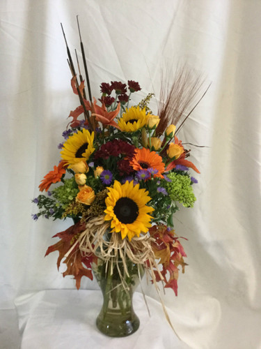 Majestic Harvest Fall Flower Bouquet from Enchanted Florist in Pasadena TX. This large beautiful fall bouquet is perfect for any office or home an includes bright yellow sunflowers, orange gerbera daisies, orange lilies, spray roses, poms, and more. RM202