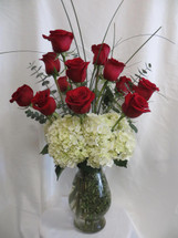 So Chic Dozen Red Roses from Enchanted Florist Pasadena TX. Our deluxe option when sending one dozen roses. It includes our upgraded Bella vase, white hydrangeas, dozen premium red Ecuadorian roses, eucalyptus, and bear grass for the flowy look. For delivery in Pearland, Webster, and surrounding areas. RM367