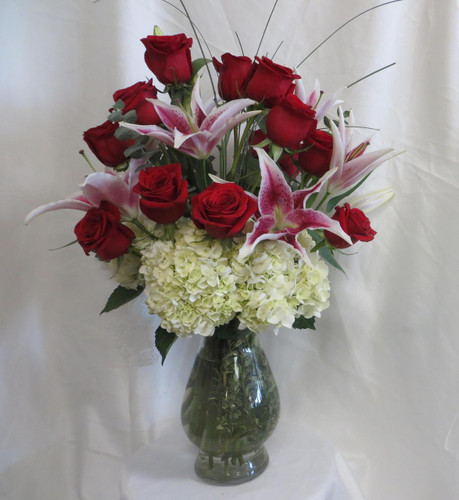 So Chic Plus Dozen Roses & Stargazers from Enchanted Florist Pasadena TX. Our Super Premium option when sending one dozen roses and you want only top of the line. It includes our upgraded Bella vase, white hydrangeas, fragrant stargazer lilies, dozen premium red Ecuadorian roses, eucalyptus, and bear grass for the flowy look for delivery in Friendswood, Webster, Pasadena, and surrounding areas. RM368