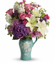 "Purple hydrangea, lavender roses, pink miniature carnations, white stock, lavender cushion spray chrysanthemums and purple seafoam statice are accented by pitta negra. Delivered in a Artisanal Beauty pitcher. Approximately 17 1/2"" W x 22 1/2"" H  17M205"
