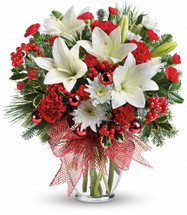 Merry All The Way Christmas Bouquet from Enchanted Florist Pasadena TX. Wish them a Happy Holiday with this seasonal display of white asiatic lilies, red carnations and holiday greens, accented with red ornaments and a glittery red ribbon. Presented in a glass vase, it is sure to please! TWR12-2
