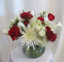 Knock Out Flower Bouquet by Enchanted Florist Pasadena TX. This lush and contemporary bouquet is artfully designed in our large Rosie Posie vase with all white flowers of calla lilies, hydrangeas, tulips, spiders, and spray roses and then accented with baby and large red roses to deliver that pop of color. A premium bouquet! Daily delivery to Friendswood. RM211
