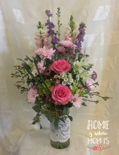 Love and Lace Pink Mothers Day Flowers by Enchanted Florist Pasadena TX.Beautiful pinks and lavender flowers in our clear lace adorned cylinder vase. Flowers include pink roses, purple larkspur, pink snapdragons, pink daisies, white alstromeria, and more. RM805