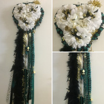 Heart Shaped Homecoming Mum by Enchanted Florist, your homecoming mums headquarters. This mum will come with 1 boa, 1 metallic chain, and 1 military braid. Trinkets on this mum will vary according to availibility. HMC102