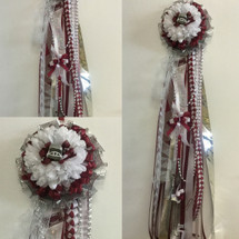 The Maroon and White Homecoming Mum from Enchanted Florist includes a single mum flower, trinkets, chains, and the Military braid in maroon and white, but can be created in the school colors of your choice. HMC113