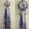 The Royal Blue and White Homecoming Mum from Enchanted Florist includes a single mum flower, trinkets, chains, and the Military braid in royal blue and white, but can be created in the school colors of your choice. HMC115