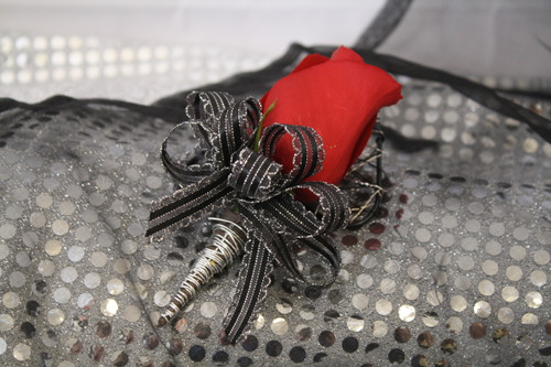 The Stud Prom Boutonniere Black and Silver with Rose by Enchanted Florist Pasadena TX. The black and silver trimmed flower match many options and includes one big rose. Also includes a matching wire bling backing.  PROM109