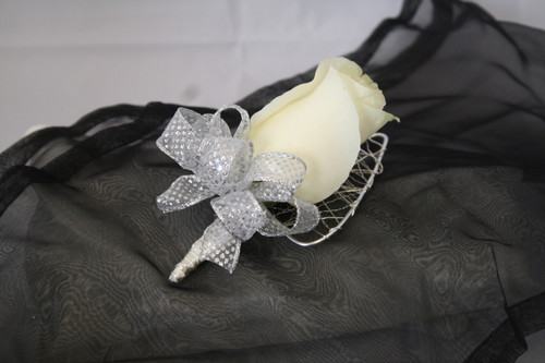 The Tatum Prom Boutonniere Silver Trim with Rose by Enchanted Florist Pasadena TX. The silver trimmed flower will match most wardrobes and includes one big rose. Also includes a matching wire bling backing. PROM110