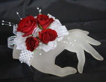 Small Iridescent Contemporary Prom Corsage by Enchanted Florist Pasadena TX. This prom corsage is on a basic pearl bracelet with red roses. PROM112