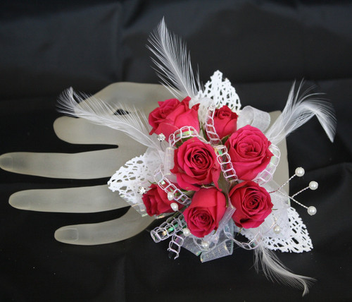 Premium Iridescent Contemporary Prom Corsage by Enchanted Florist Pasadena TX. This premium prom corsage is on a basic pearl bracelet with white lace leaves, pearl bling, diamond bling and feathers with hot pink roses. PROM113