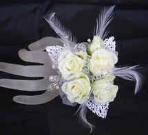 Premium Iridescent Contemporary Prom Corsage by Enchanted Florist Pasadena TX. This premium prom corsage is on a basic pearl bracelet with white lace leaves, pearl bling, diamond bling and feathers with white roses. PROM113