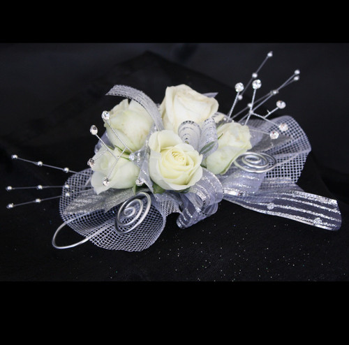 Basic All Silver Traditional Prom Corsage by Enchanted Florist Pasadena TX. This basic prom corsage is our traditional corsage design built on wire to fit every size wrist, perfect for the small sizes. Includes basic bling in silver colored trim with white roses. PROM114