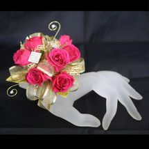 Premium Gold Contemporary Prom Corsage by Enchanted Florist Pasadena TX. This premium prom corsage is on a gold bling bracelet with gold leaves, rhinestone bling, gold swirls and a gold butterfly. Pictured with hot pink roses.  PROM115
