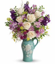 "Crème roses, lavender alstroemeria, purple stock, purple button spray chrysanthemums, lavender cushion spray chrysanthemums, and white limonium are accented with bupleurum and huckleberry. Delivered in an Artisanal Beauty pitcher. Approximately 17 1/2"" W x 22 1/2"" H  17M200 RM818"