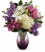 "White oriental lilies, white hydrangea, lavender stock, and purple alstroemeria are accented with spiral eucalyptus and lemon leaf. Delivered in an All Eyes On You vase. Approximately 16 1/2"" W x 19"" H  18M205"