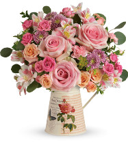 "This chic bouquet includes pink roses, peach spray roses, white alstroemeria, pink miniature carnations, lavender cushion spray chrysanthemums, bupleurum, oregonia, and silver dollar eucalyptus. Delivered in a Mod Mademoiselle pitcher. Approximately 15 1/4"" W x 14 1/4"" H  19M305"