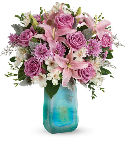"This bouquet features lavender roses, pink stargazer lilies, light pink alstroemeria, lavender cushion spray chrysanthemums, lavender limonium, dusty miller, parvifolia eucalyptus, and lemon leaf. Delivered in an Art Glass Treasure vase. Approximately 18 1/2"" W x 19 1/4"" H  19M500"