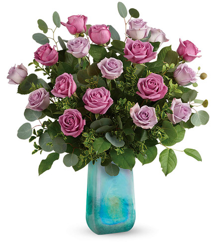 "This gorgeous bouquet includes lavender roses, silver dollar eucalyptus, oregonia and lemon leaf. Delivered in an Art Glass Treasure vase. Approximately 20"" W x 22 1/2"" H  19M510 RM824"