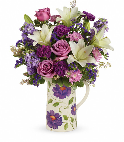 """This garden-inspired bouquet features lavender roses, white oriental lilies, purple carnations, lavender stock, lavender cushion spray chrysanthemums, lavender sinuata statice, seeded eucalyptus and variegated pittosporum. Delivered in a Garden Pitcher. Approximately 17 1/2"""" W x 22 1/4"""" H  16M200 RM825"""