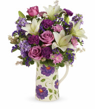 "This garden-inspired bouquet features lavender roses, white oriental lilies, purple carnations, lavender stock, lavender cushion spray chrysanthemums, lavender sinuata statice, seeded eucalyptus and variegated pittosporum. Delivered in a Garden Pitcher. Approximately 17 1/2"" W x 22 1/4"" H  16M200 RM825"