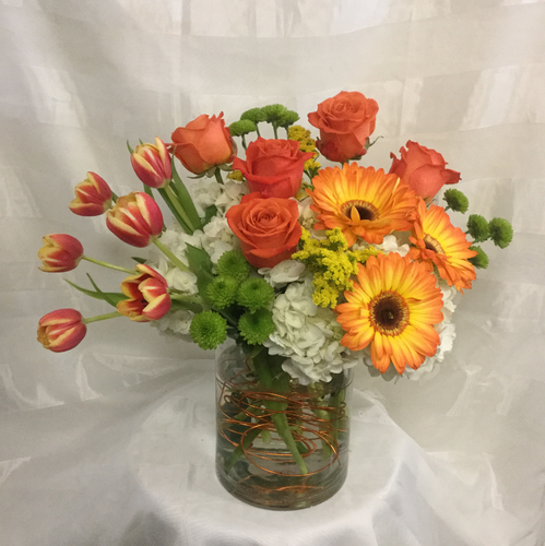 Orange You Glad She's Your Mom by Enchanted Florist Pasadena TX. This lovely orange bouquet is not for the traditional mom, but a great spunky mom who loves everything bright and sunny. It includes orange roses, orange tulips, yellow or orange gerbera daisies, white hydrangeas and green viking poms in a cylinder vase.  RM807