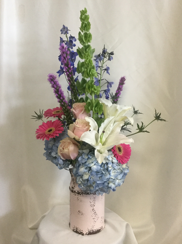 Mother's Day Milk Jug Bouquet of Flowers by Enchanted Florist Pasadena TX. A mother's day flower arrangement as special as she is. This will include a mixture of lilies, gerbera daisies, roses, delphinium, hydrangeas and bells of ireland in our exclusive large milk jug vase. Color of vase may vary.  RM816
