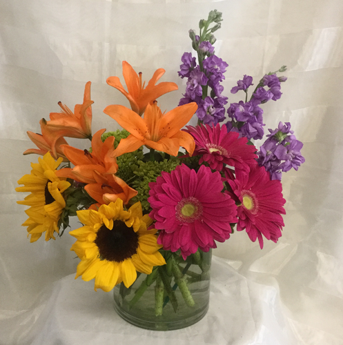 Brighten Her Day Mom's Bouquet by Enchanted Florist Pasadena TX. A bright and lovely bouquet for any mom to enjoy. It includes orange lilies, purple stock, pink gerberas, sunflowers and green hydrangeas designed in a clear cylinder vase. RM809