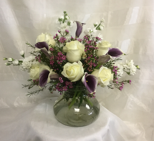 White Elegance and Grace Mother's Day Flowers by Enchanted Florist Pasadena TX. This elegant white and purple bouquet includes white roses, purple calla lilies, and white stock accented with purple wax flower and is arranged in our large rosie posie vase. RM808