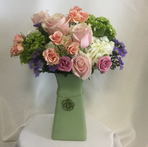Green Envy Mother's Day Bouquet by Enchanted Florist Pasadena TX. This bouquet will make all her friends or co-workers envious. A lovely bouquet of fresh flowers in a unique vase with rose accent. It includes a variety of pink roses, green and white hydrangeas and purple accents.  RM815