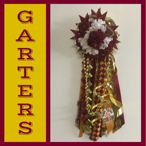 The Maroon and Gold Homecoming Garter from Enchanted Florist includes a single garter flower, trinkets, metallic chain, the military and diamond braid, and garter band in the school colors of your choice. HMC154
