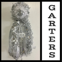 The Deluxe Senior Homecoming Garter in Silver from Enchanted Florist includes a single garter flower, trinkets, metallic chain, the Military braid and garter band in the school colors of your choice. HMC151